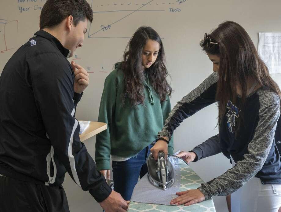 "Trinity School senior Isabella Garriga learns to iron as Saloni Cholia and Preston Picciano watch 03/07/2019 as seniors learn some ""life skills"" at Trinity School. Tim Fischer/Reporter-Telegram Photo: Tim Fischer"
