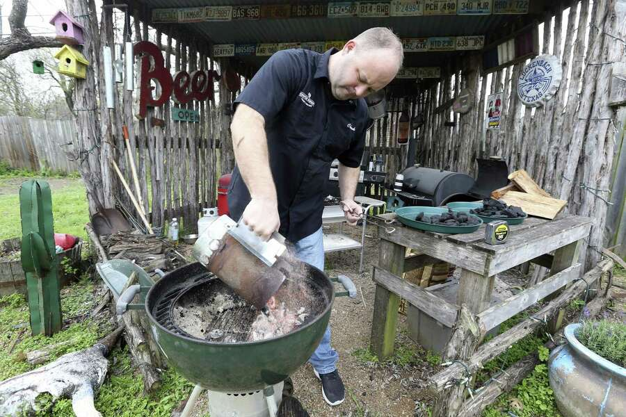 Chuck Blount pours charcoal briquettes from a chimney starter into a Weber grill as he prepares to grill chicken and sausage with an off-set fire, with all the briquettes placed on one side of the grill.