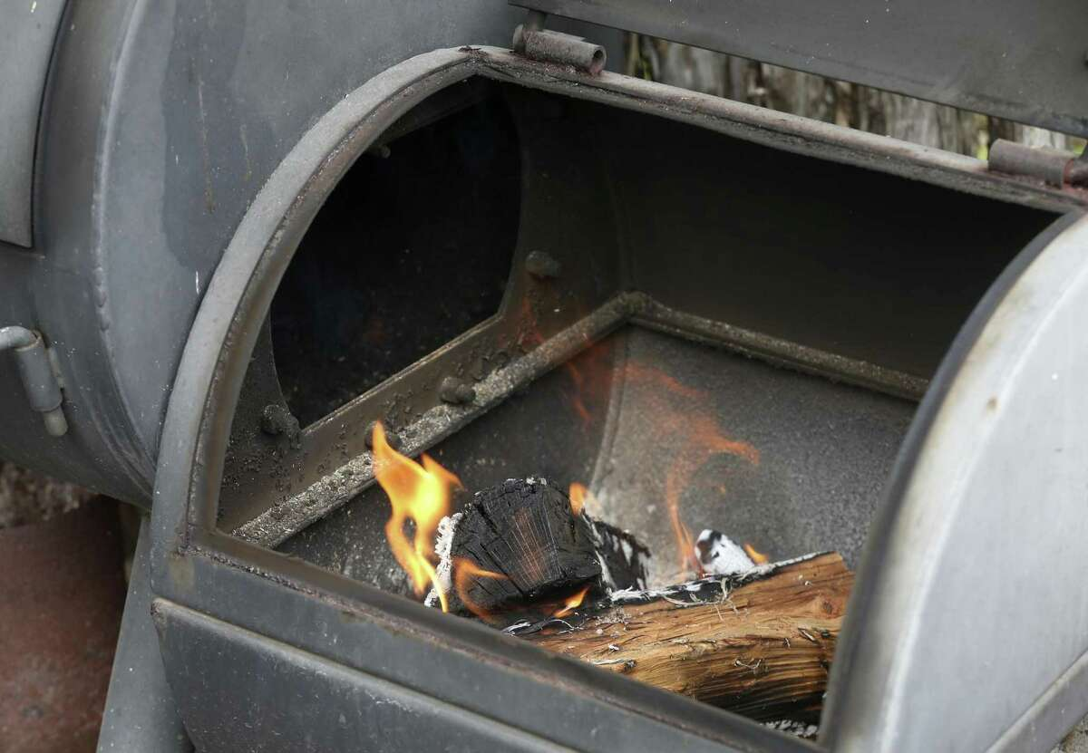 Two split logs rest on a small pile of charcoal briquettes to get an offset smoker to the correct 250 degree temperature.