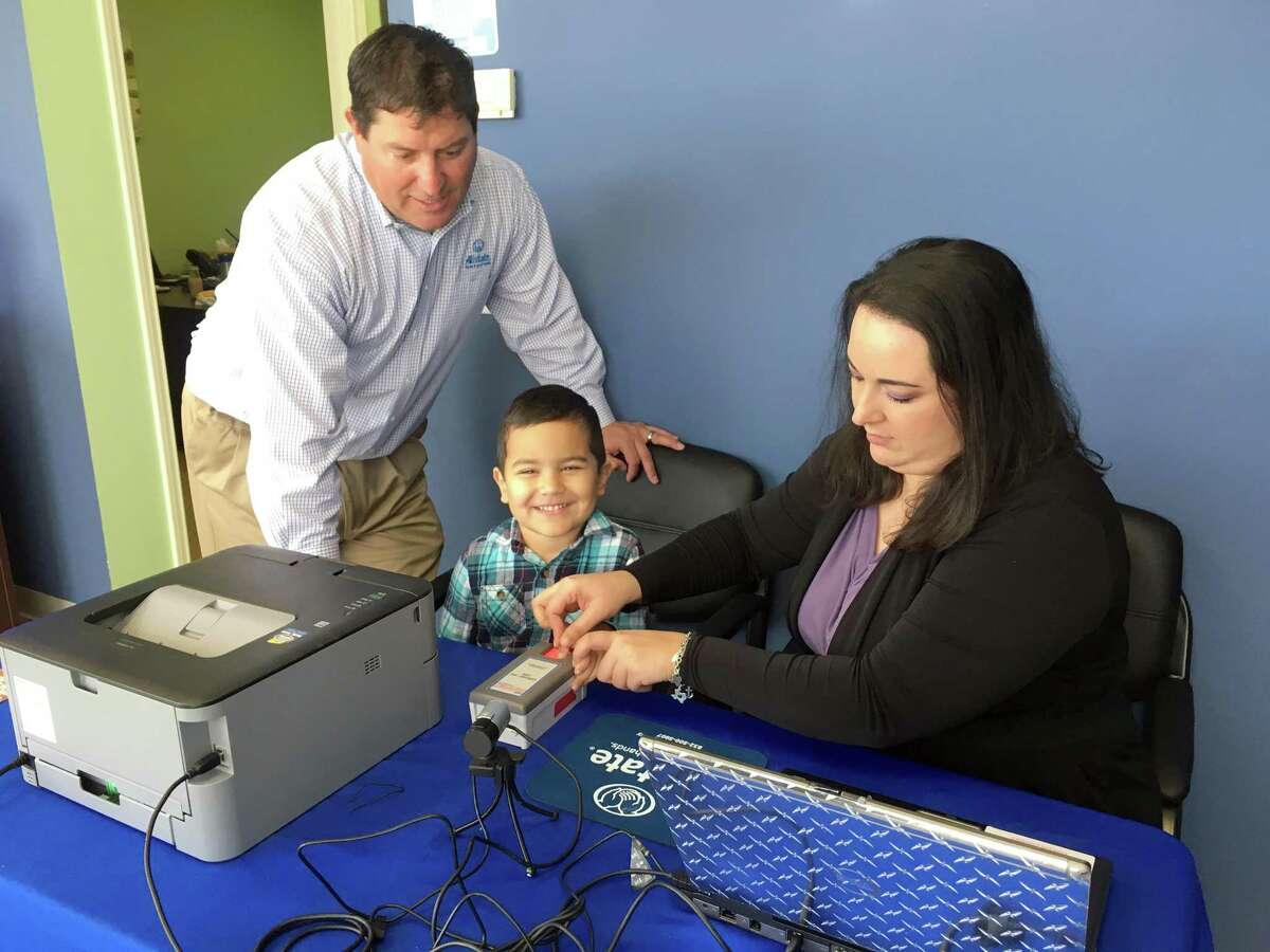 Allstate Agency Owner Eric Arredondo (pictured at left) watches as four year-old Xander Herrera (center) is finger-printed by Allstate LSP (and mom) Karym Herrera (right) as part of the new Operation Kidsafe Year-Round Child Safety Center p;rogram. A grand opening celebration was held Friday, March 8, at the new Sugar Land location.