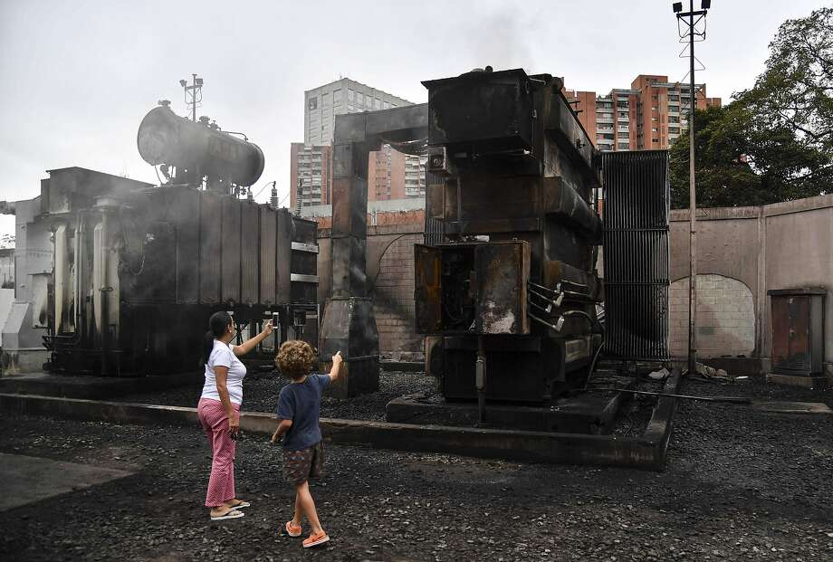 A woman and child check out a power substation damaged by a blast in Caracas, Venezuela. Photo: Yuri Cortez / AFP / Getty Images