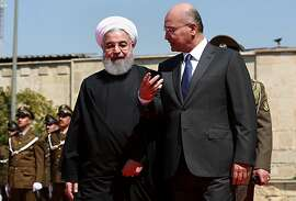 Iraqi President Barham Salih, right, walks with visiting Iranian President Hassan Rouhani, before their meeting at Salam Palace in Baghdad, Iraq, Monday, March 11, 2019. Rouhani is visiting Iraq, seeking to boost ties between the two neighboring states and possibly secure Iraq's help in bypassing U.S. sanctions the Trump administration re-imposed last year. (AP Photo/Khalid Mohammed)
