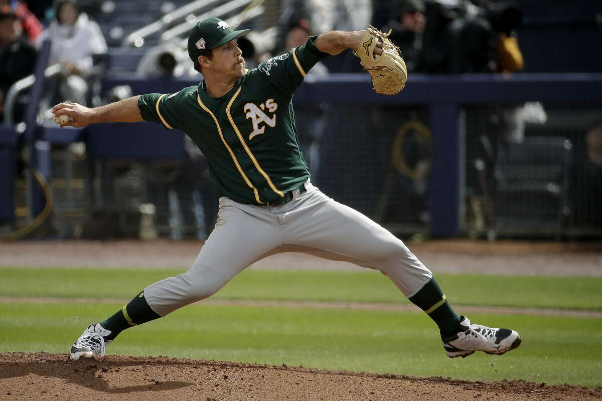 Oakland Athletics starting pitcher Daniel Mengden throws during the first inning of a spring training baseball game against the Seattle Mariners, Friday, Feb. 22, 2019, in Peoria, Ariz. (AP Photo/Charlie Riedel)