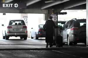 A traveler returns to her vehicle at the Albany International Airport parking garage on Monday, March 11, 2019, in Colonie, N.Y. (Will Waldron/Times Union)