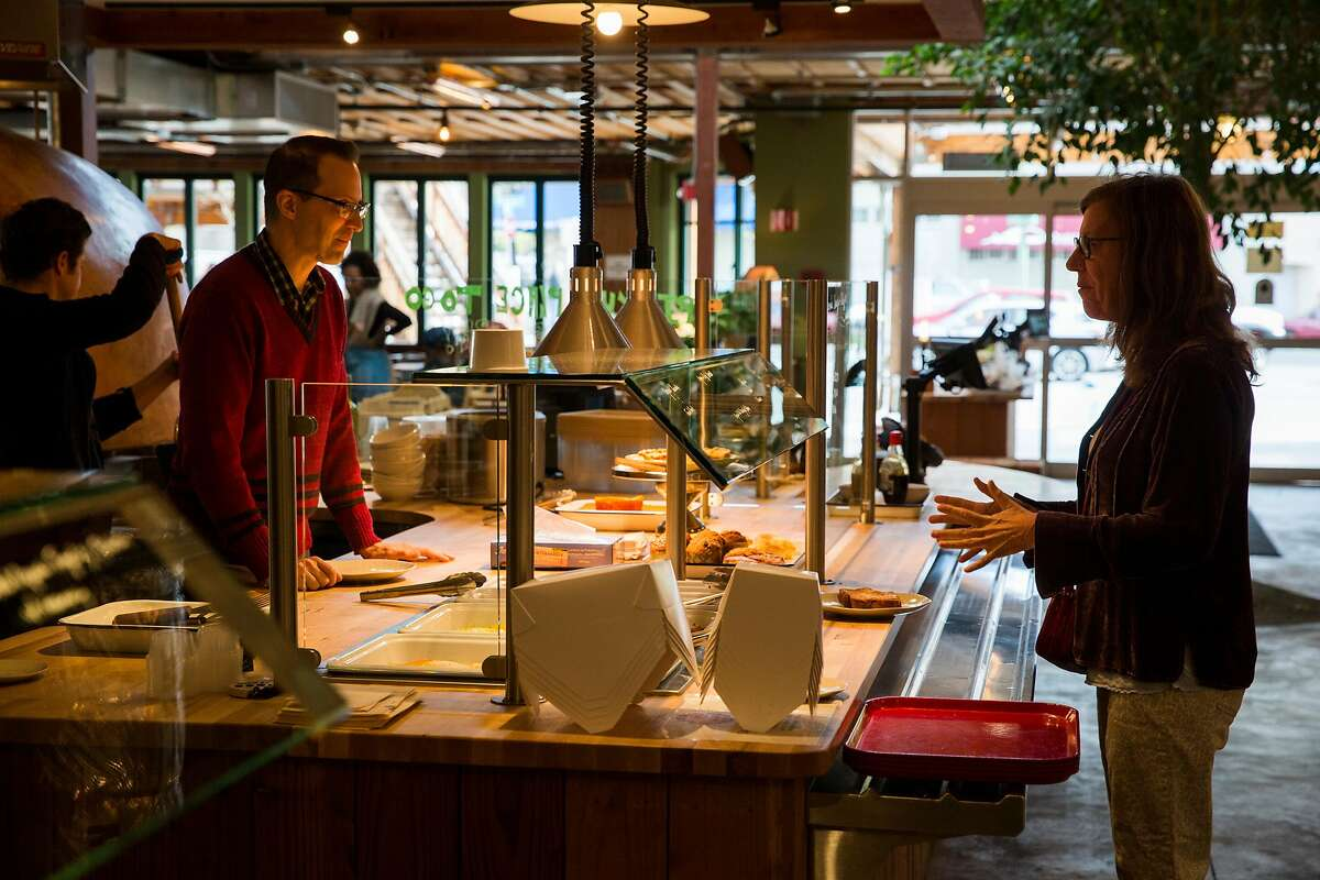 A customer converses with a staff member at hot food bar area at Chow in Oakland, Calif. on Monday, April 2, 2018.