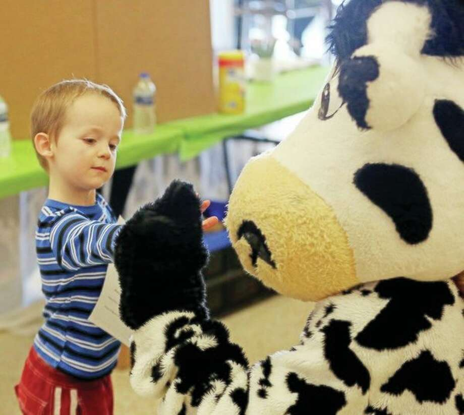 Mikey McCue, 6 of, Caseville, fist bumps the Dairy Zone cow, representing Zwemmer Dairy Farms, Saturday, during the Huron Daily Tribune's Healthy Living Expo. Formore photos from the event, see Page 8A. (Paul P. Adams/Huron Daily Tribune)