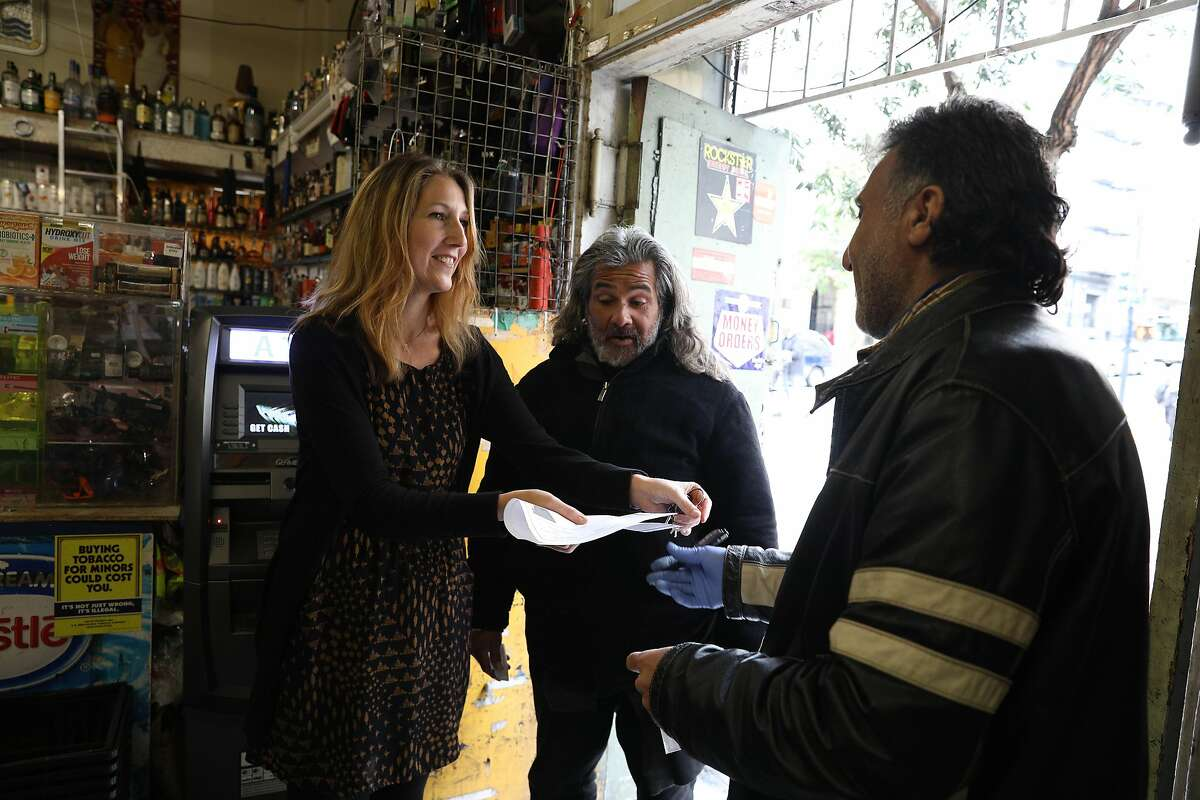 Rachel Rodriguez (l to r), director and co-founder Community Payee Partnership, and client Thomas Soto talk with Moe Najjar, Ser-Well Market Liquors staff, as they check in regarding Soto's store account on Thursday, March 7, 2019 in San Francisco, Calif.