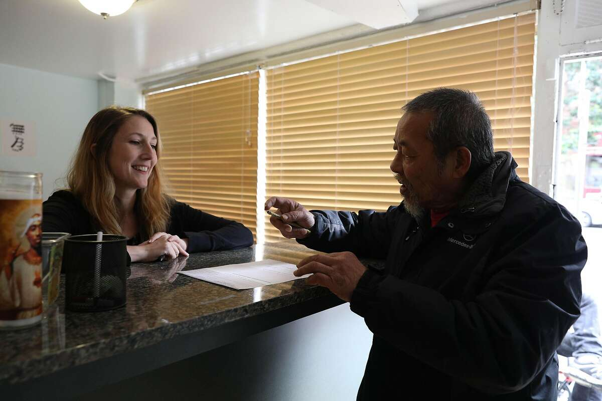 Rachel Rodriguez (l to r), director and co-founder Community Payee Partnership, talks with client Louie Yip as he picks up a check at a Community Payee Partnership office on Thursday, March 7, 2019 in San Francisco, Calif.