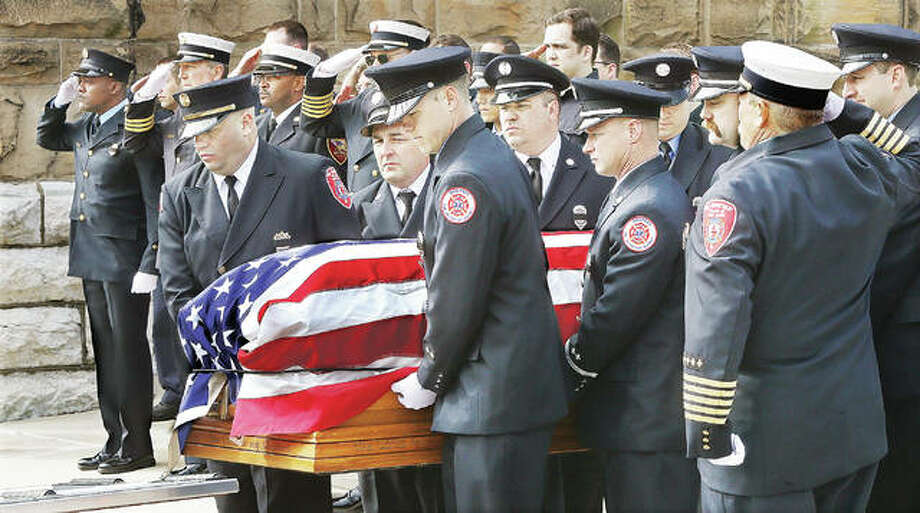 "It was a solemn event Monday as firefighters unloaded the flag draped casket of Jacob ""Jake"" Ringering at St. Mary's Catholic Church in Alton ahead of his visitation Monday afternoon. About 40 firefighters from the area stood at attention in dress uniform and saluted their fallen comrade as he was carried into the church. Hundreds of people attended the visitation for Ringering who died battling a house fire last week on Culp Lane near Bethalto. Photo: John Badman 