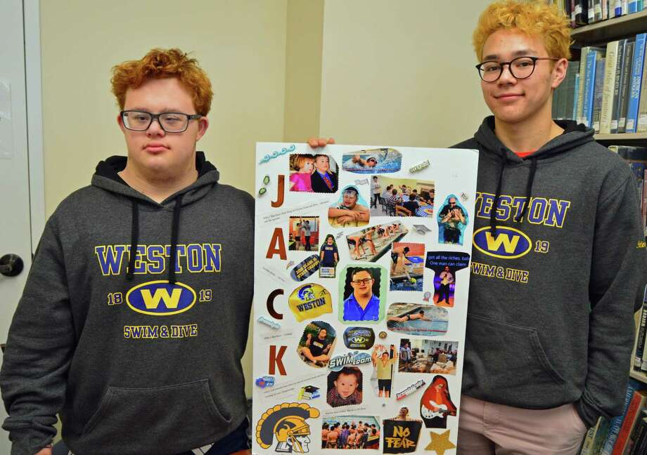 Jack Piscitell and his teammate, Oscar Petersen, hold up the poster board that Piscitell and his mother, Cathleen Crowley-Piscitell, made for senior night, which consisted of many pictures of Piscitell growing up and swimming, on March 2 at the Weston Library. Photo: Nicole Zappone / For Hearst Connecticut Media /