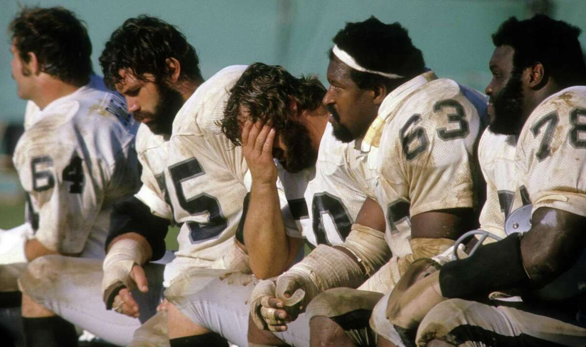 CIRCA 1970's: Offensive tackle John Vella #75, center Dave Dalby #50 with their heads down as teammates Art Shell #78, guard Gene Upshaw #63 of the Oakland Raiders watches the action from the bench circa 1970's during an NFL football game. Shell played for the Raiders from 1968-82. (Photo by Focus on Sport/Getty Images)