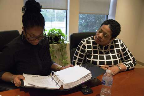 Karen Miniex, right, and her attorney Zenobia Bivens look over exhibitions while discussing her lawsuit against the Houston Housing Authority with the Houston Chronicle on Thursday, March 7, 2019, in Houston. Miniex alleges the Housing Authority retaliated against her after she blew the whistle on fraud.