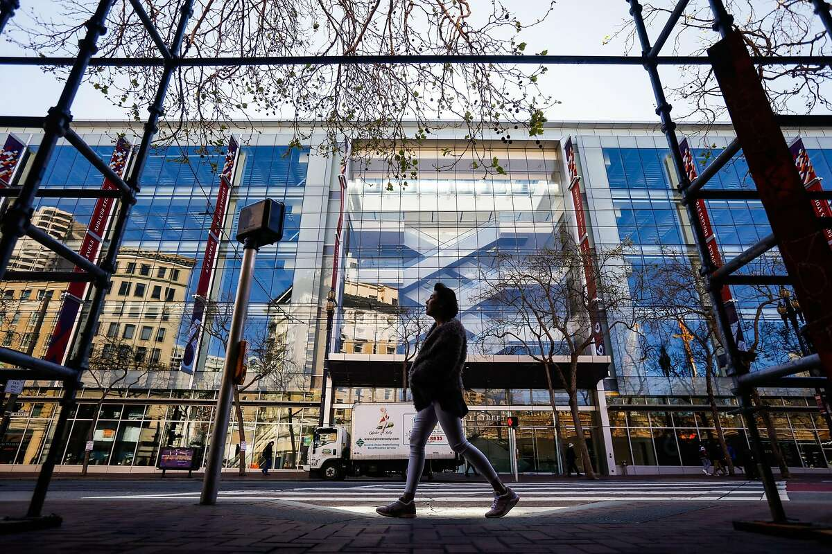 Jasmin Chiu, who is visitng from Hong Kong walks on Market Street passing by the 6x6 Mall in San Francisco, California, on Monday, March 11, 2019. It was considered as a potential site for a new navigation center for the homeless.