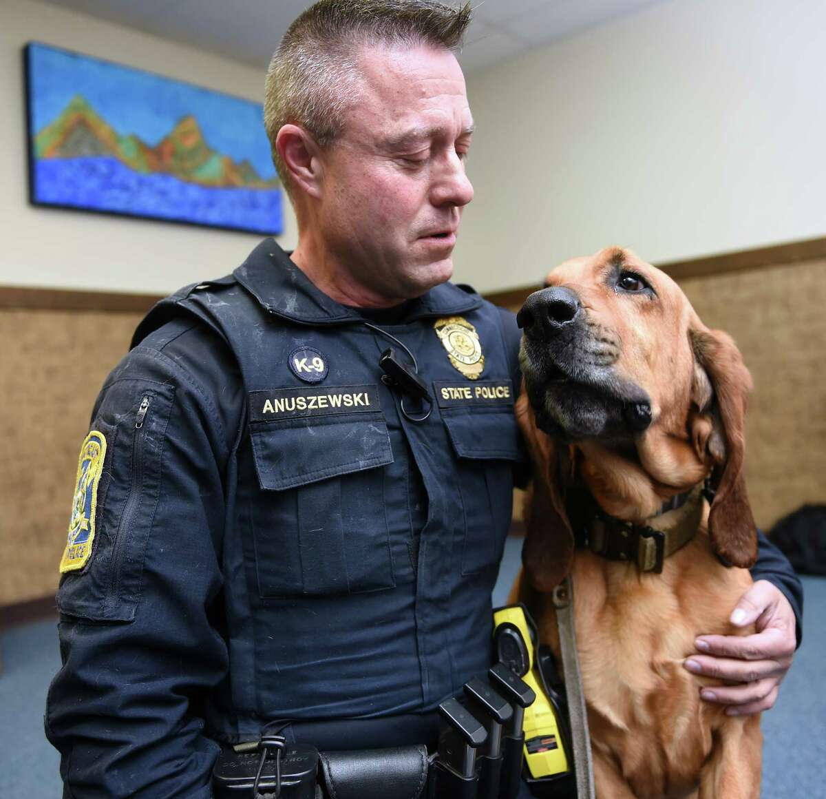 Connecticut State Police Trooper 1st Class Edward Anuszewski is photographed with his bloodhound tracking dog, Texas, at the Connecticut State Police Canine Unit Training Center in Meriden on March 11, 2019.