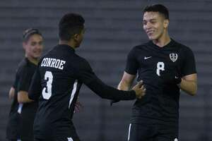 Josue Fuentes #8 of Conroe give a high-five to Misael Martinez after Martinez' goal during the first period of a non-district high school soccer match at Buddy Moorhead Stadium, Wednesday, Jan. 16, 2019, in Conroe.