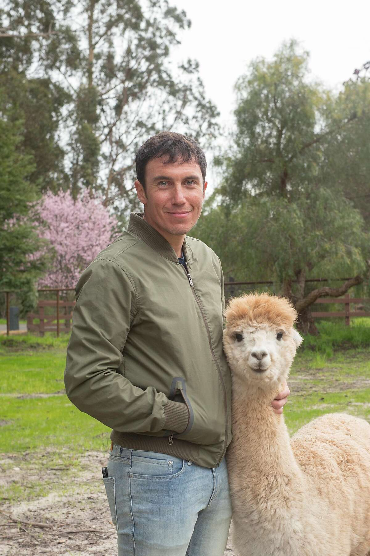 Photographer Chris Burkard with one of his two pet alpacas at his home in Arroyo Grande, Calif.