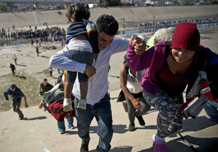 In November, migrants walk up a riverbank at the Mexico-U.S. border at the Chaparral border crossing in Tijuana, Mexico. Border policy isn't about keeping out opioids, turning back criminals and rescuing children from traffickers. It's about changing demographics. Photo: Ramon Espinosa /Associated Press / Copyright 2018 The Associated Press. All rights reserved.