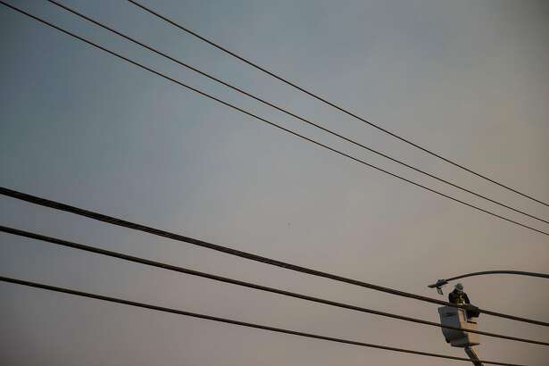 FILE - A utility worker repairs a power line in Paradise, Calif., Nov. 16, 2018, after the Camp Fire, the state's deadliest wildfire, which led to an investigation of Pacific Gas & Electric's responsibility. PG&E, which filed for bankruptcy in January, has been blamed for deadly explosions and wildfires, but lawmakers continue to benefit from political donations from the company. (Eric Thayer/The New York Times)
