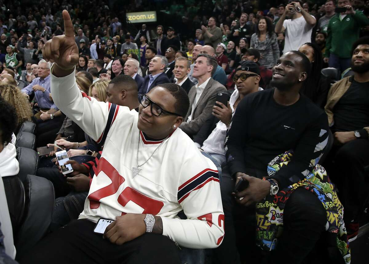 New England Patriots football player Trent Brown (77) acknowledges the fans as the Patriots' Super Bowl victory is honored during a break in an NBA basketball game between the Boston Celtics and the Los Angeles Lakers, Thursday, Feb. 7, 2019, in Boston. (AP Photo/Elise Amendola)