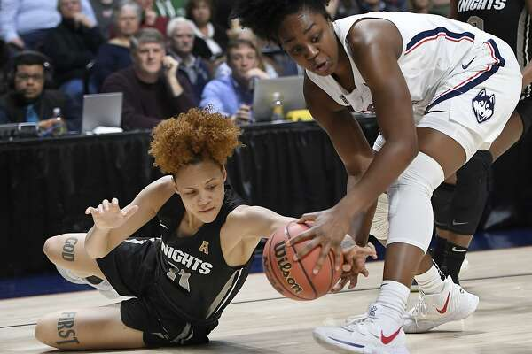 Central Florida's Kayla Thigpen, left, and Connecticut's Christyn Williams reach forthe ball during the first half of an NCAA college basketball game in the American Athletic Conference women's tournament finals, Monday, March 11, 2019, at Mohegan Sun Arena in Uncasville, Conn. (AP Photo/Jessica Hill)