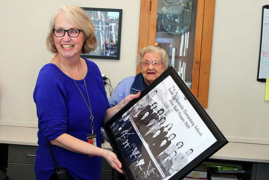 School secretary Rachael Jones (left) holds copy of the first South Jacksonville Elementary School staff photo from 1949. Frances Kirchhofer (right) noticed the photo — and pointed out that she was in it — when she was visiting the newly renovated front offices at the school during an open house Monday. Kirchhofer was a music and band teacher at the time the photo was taken. The renovation of the front offices and entry way make the school more secure, but also incorporated parts of the original facade and columns in the new design. Photo: Rosalind Essig | Journal-Courier