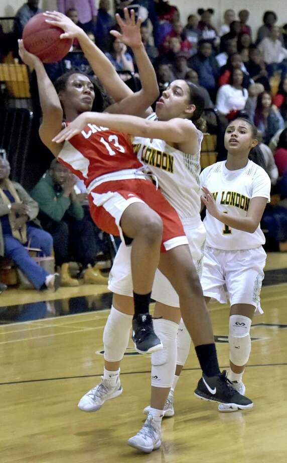 Wilbur Cross' Aniaja Ricks is fouled by New London's KD Spencer Roman during the fourth quarter Monday. Photo: Peter Hvizdak / Hearst Connecticut Media / New Haven Register