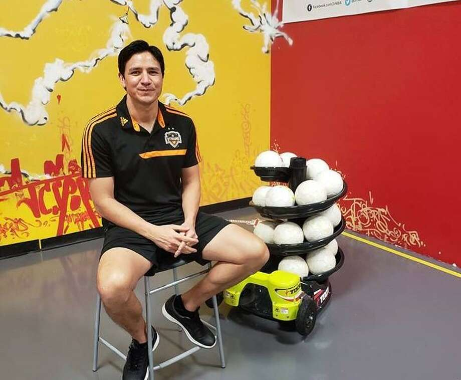 Former Houston Dynamo player Brian Ching poses next to a TOCA touch trainer. Photo: Courtesy Of JC Sports Houston