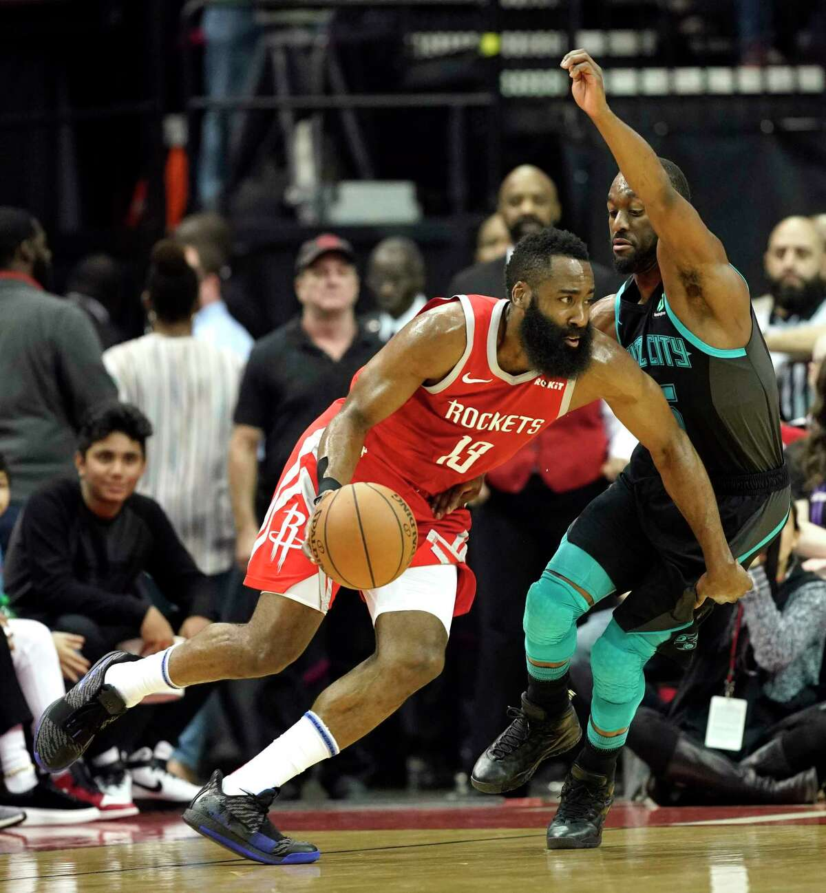 Houston Rockets' James Harden (13) drives toward the basket as Charlotte Hornets' Kemba Walker defends during the first half of an NBA basketball game Monday, March 11, 2019, in Houston. (AP Photo/David J. Phillip)
