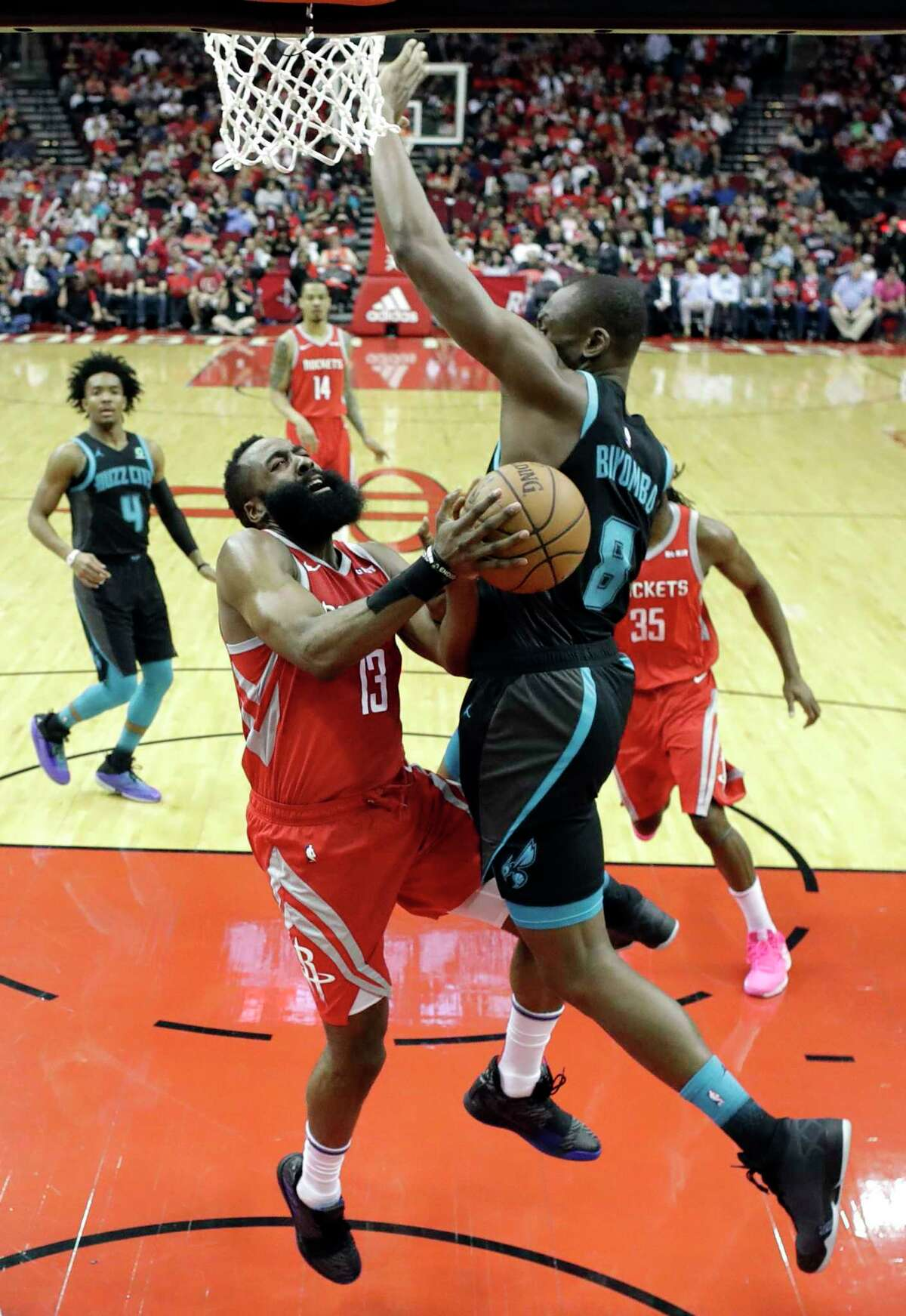 Houston Rockets' James Harden (13) is fouled by Charlotte Hornets' Bismack Biyombo (8) during the first half of an NBA basketball game Monday, March 11, 2019, in Houston. (AP Photo/David J. Phillip)