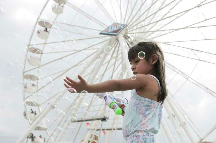 Mia Santana, 3, of Houston chases down bubbles on the midway at the Houston Livestock Show and Rodeo on  Monday, March 11, 2019 in Houston. Photo: Elizabeth Conley, Staff Photographer / © 2018 Houston Chronicle