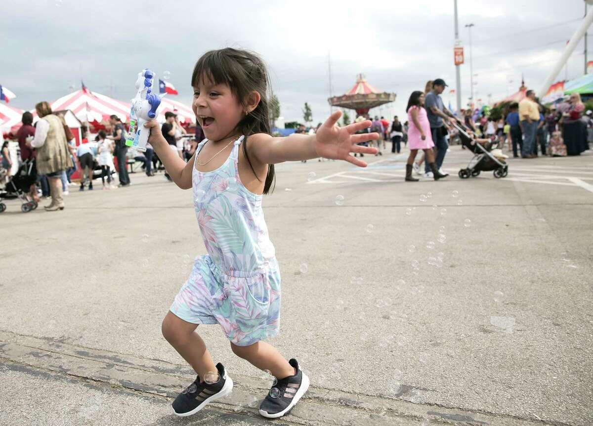 Mia Santana, 3, of Houston chases down bubbles on the midway at the Houston Livestock Show and Rodeo on Monday, March 11, 2019 in Houston.