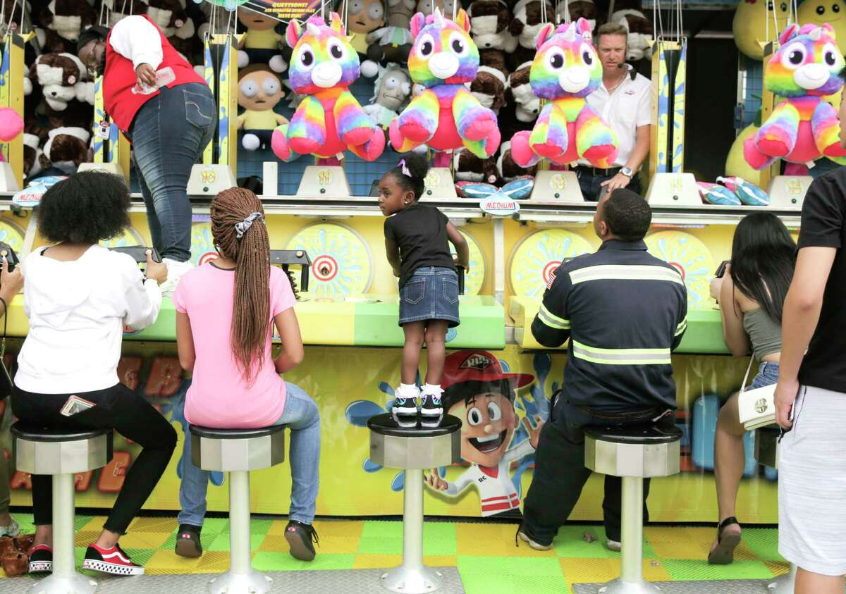 Royaltee Manuel, 3, of Houston gets a better view as she competes for a stuffed animal on the midway at the Houston Livestock Show and Rodeo on Monday, March 11, 2019 in Houston.
