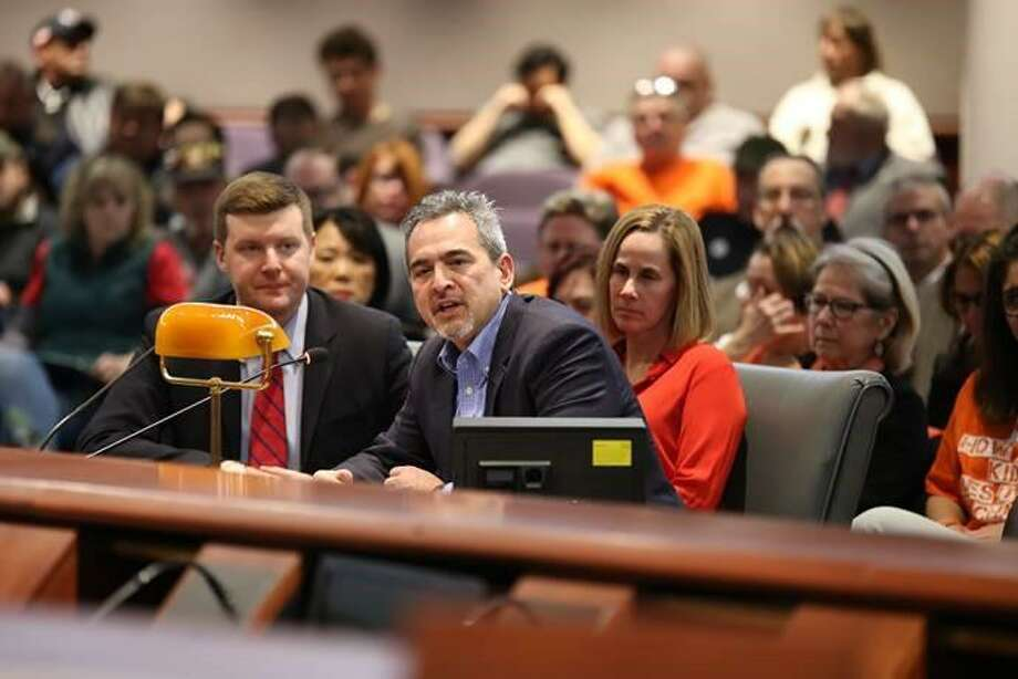 Michael Song testifies Monday on gun legislation. His wife, Kristin Song, is in orange behind him. Their song accidentally shot himself in Guilford in early 2018. Photo: Christine Stuart / CTNewsJunkie.com