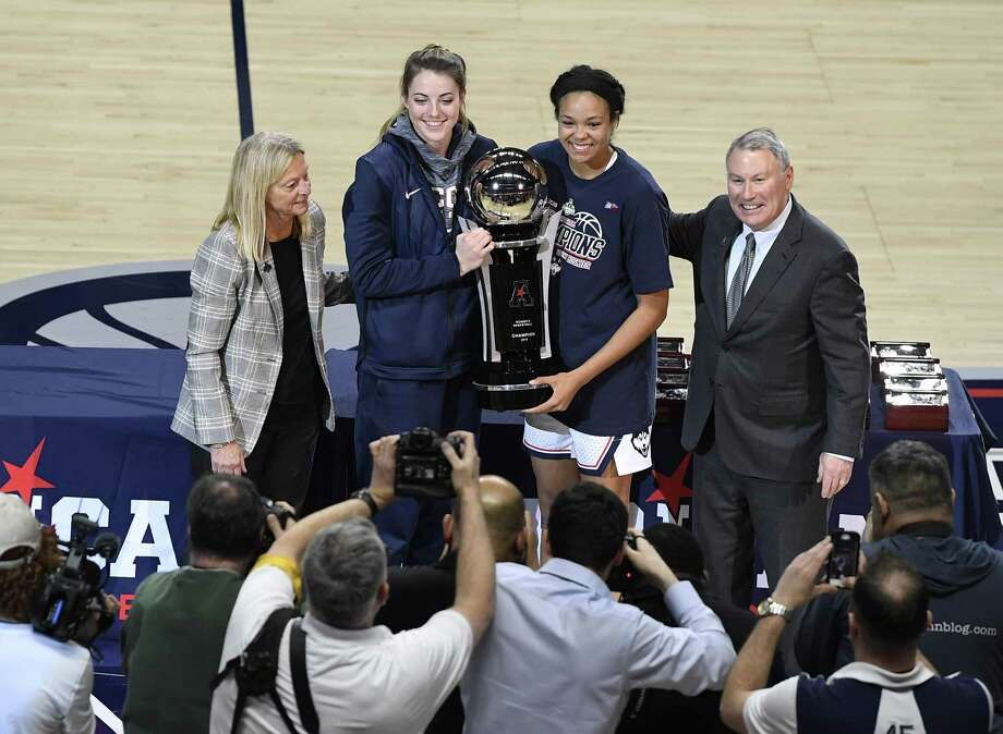 Katie Lou Samuelson, second from top left, and Napheesa Collier, second from top right, hold the American Athletic Conference women's tournament championship trophy presented by associate commissioner for women's basketball Barbara Jacobs and commissioner Mike Aresco after defeating UCF in the AAC women's tournament finals March 11 at Mohegan Sun Arena. Photo: Jessica Hill / Associated Press / Copyright 2019 The Associated Press. All rights reserved
