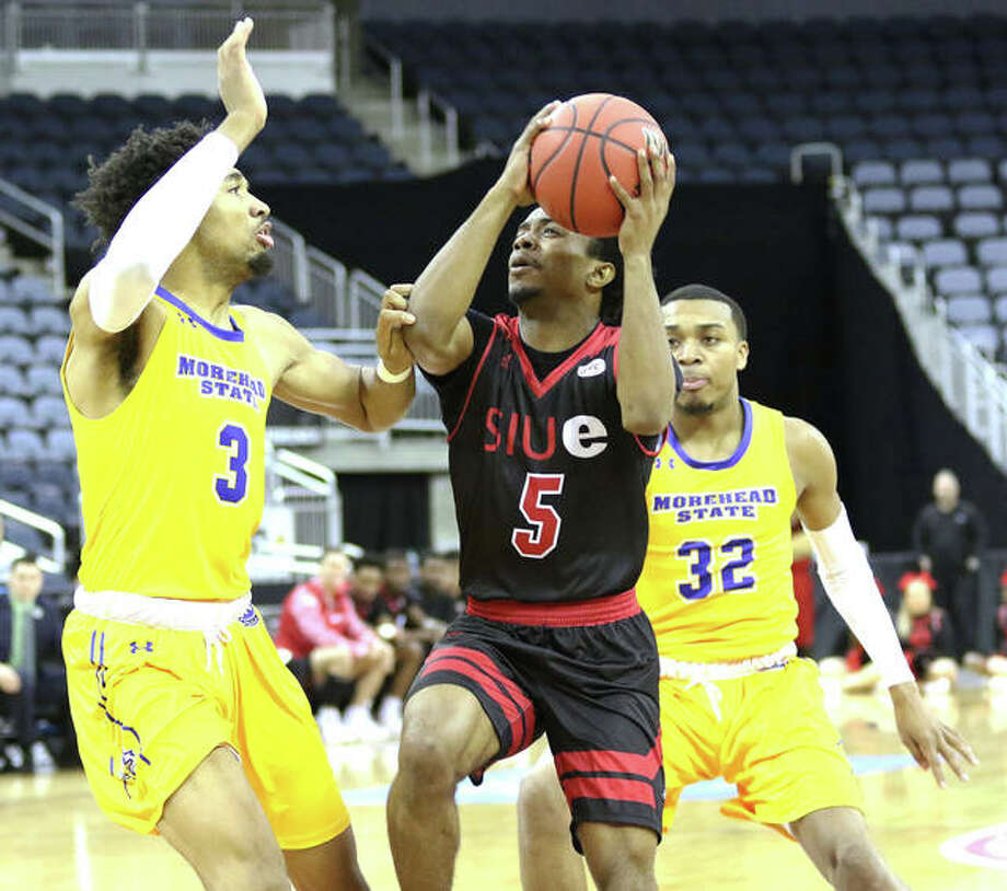 SIUE's Tyreese Wlliford (5) goes up for a shot between Morehead State's James Baker (3) and Djimon Henson on Wednesday night in a first-round game at the Ohio Valley Conference Tourney in Evansville.