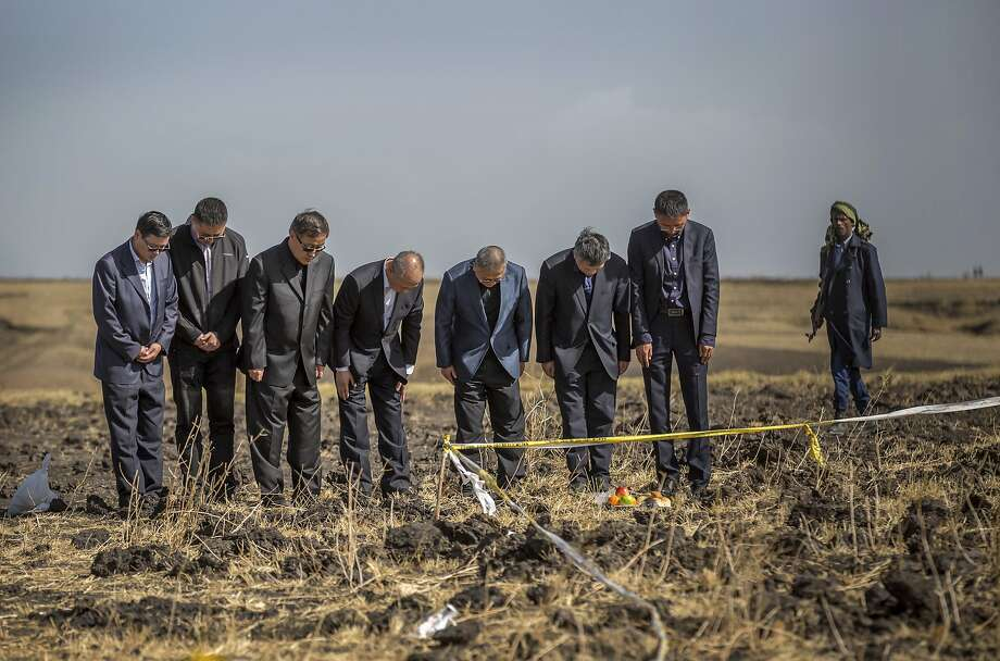 Chinese aviation officials pray at the scene where an Ethiopian Airlines jet crashed south of Addis Ababa. Photo: Mulugeta Ayene / Associated Press