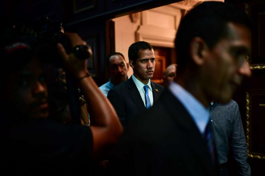 """TOPSHOT - Venezuelan opposition leader and self-proclaimed acting president Juan Guaido (C) arrives at the Venezuelan National Assembly in Caracas on March 11, 2019. - Venezuela's opposition leader Juan Guaido will ask lawmakers on Monday to declare a """"state of alarm"""" over the country's devastating blackout in order to facilitate the delivery of international aid -- a chance to score points in his power struggle with President Nicolas Maduro. (Photo by RONALDO SCHEMIDT / AFP)RONALDO SCHEMIDT/AFP/Getty Images Photo: RONALDO SCHEMIDT;Ronaldo Schemidt / AFP / Getty Images"""