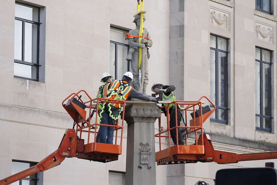 Workers begin removing a Confederate statue from its location in downtown Winston-Salem, N.C., The action is considered a rare move since such monuments are largely protected by law. Photo: Skip Foreman / Associated Press
