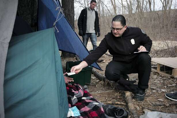 In this Tuesday, Feb. 12, 2019 photo Worcester Police officer Angel Rivera, right, returns a license to an unidentified man as Rivera asks if he has been tested for Hepatitis A at the entrance to a tent where the man spent the night in a wooded area, in Worcester, Mass. Dan Cahill, City of Worcester sanitary inspector, walks behind center. The city was hit hard when recent hepatitis A outbreaks across the country started sickening and killing homeless people and illicit drug users. (AP Photo/Steven Senne)