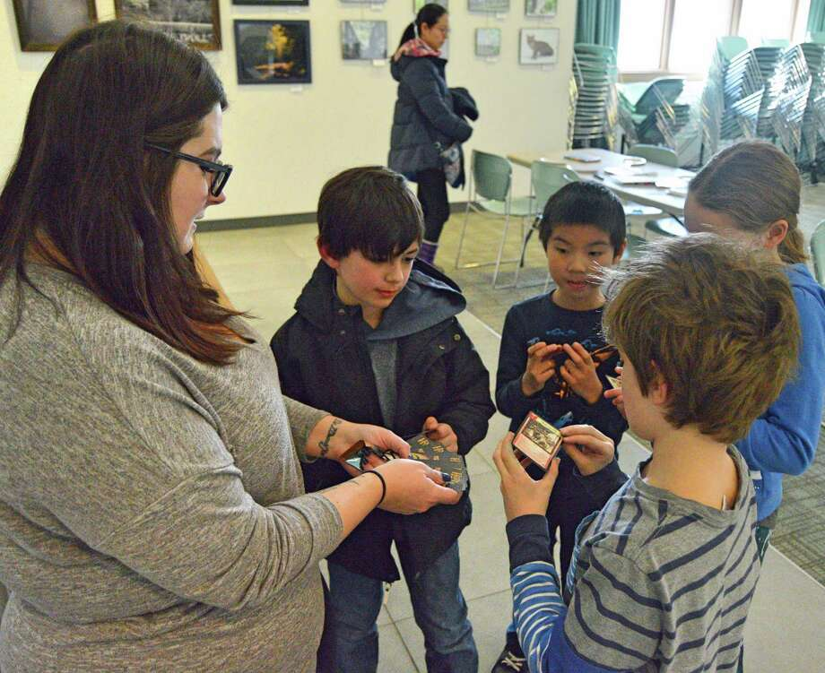 Kids gather around children's librarian Alessandra Petrino as they await their turn to select a playing card during the monthly Harry Potter club meeting at Weston Public Library, March 7, 2019. Photo: Nicole Zappone / For Hearst Connecticut Media