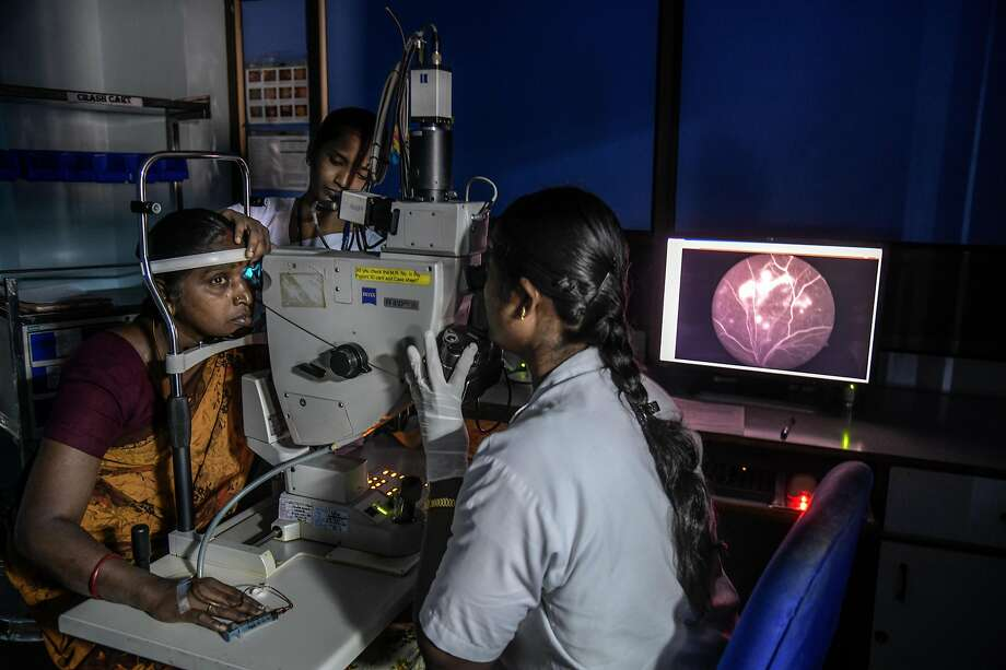 Medical personnel at the Aravind Eye Hospital perform an eye exam on a patient in Madurai, India. Photo: Photos By Atul Loke / New York Times