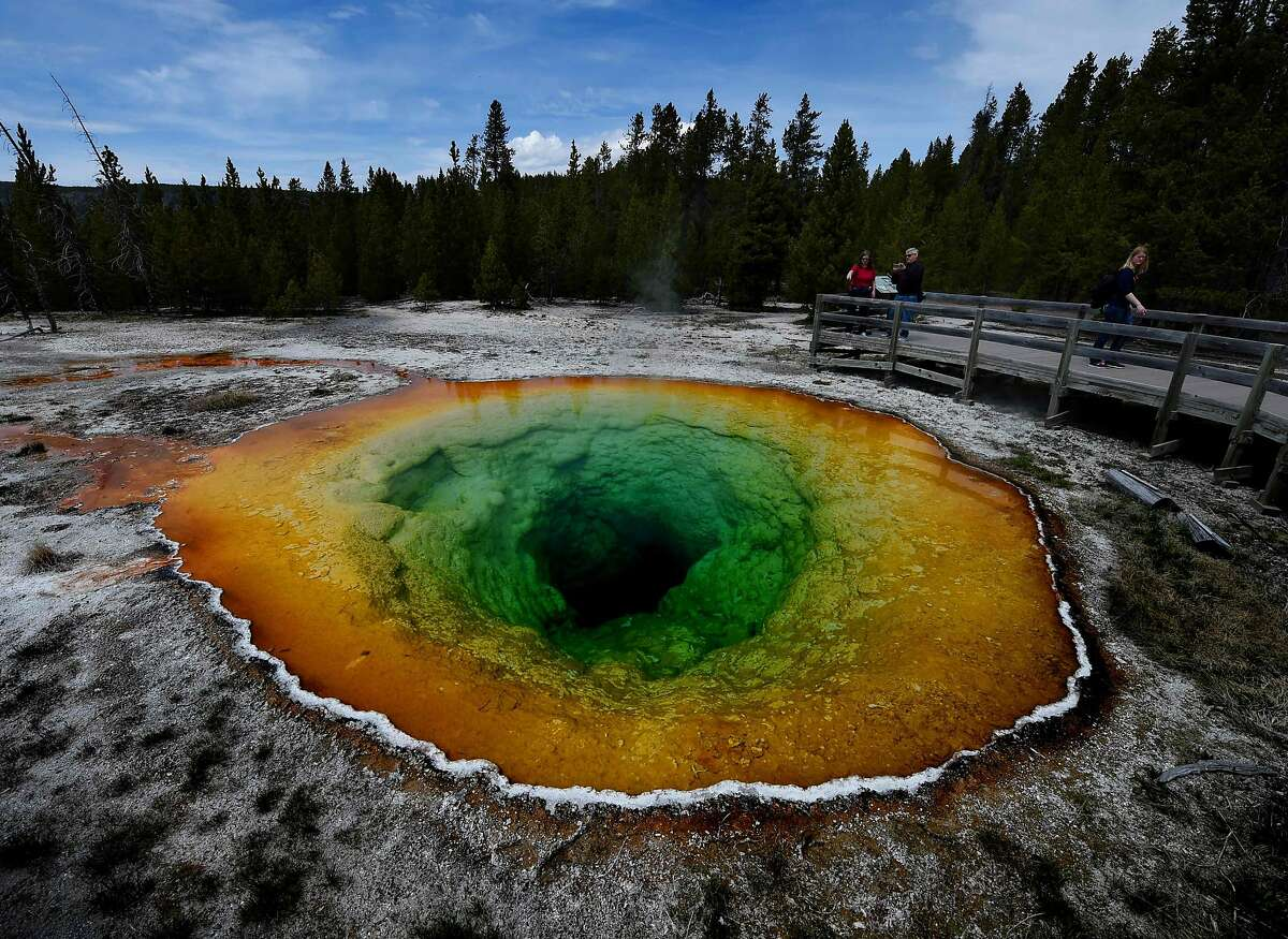 (FILES) In this file photo taken on May 13, 2016 tourists view the Morning Glory hot spring in the Upper Geyser Basin of Yellowstone National Park in Wyoming. - The US Senate approved a landmark expansion of protected lands on February 12, 2019, the first major gain for conservationists in two years after repeated setbacks by the Trump administration. The Senate voted 98-2 in support of the Natural Resources Management Act, which gives new or strengthened protection from mining and encroachment to more than two million acres (810,000 hectares), expands eight national parks and historic sights, and adds new national monuments and heritage areas. (Photo by Mark Ralston / AFP)MARK RALSTON/AFP/Getty Images