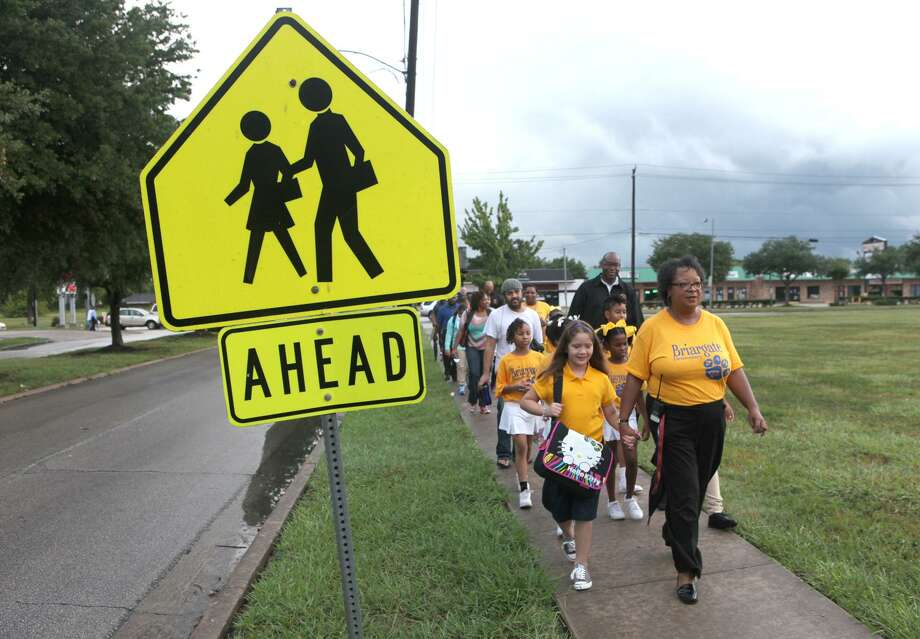 The Cy-Fair ISD school board voted to allow Harris County MUD No. 10 the use of land to build a sidewalk next to Goodson Middle School. Shown here: Briargate principal Valerie Maclin holds the hand of Audra Mancha 8 as she leads children and parents down the sidewalk on the way to school as part of the walking school bus in Missouri City. (Photo by Alan Warren) Photo: Photo By Alan Warren, Staff Photographer / Houston Community Newspapers / Houston Community Newspapers