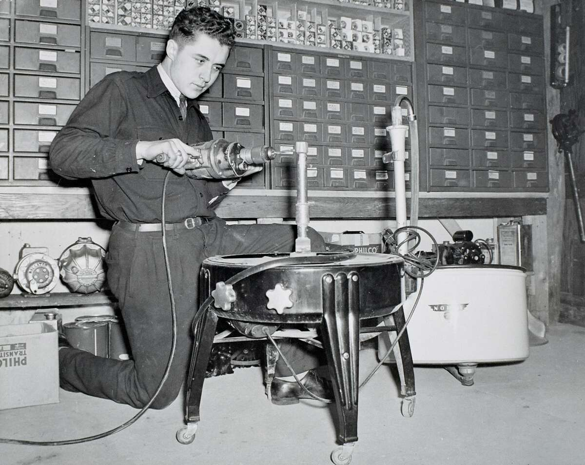 A young Earl B. Feiden assembles what appears to be a wringer washing machine. (Earl B. Feiden Appliances)