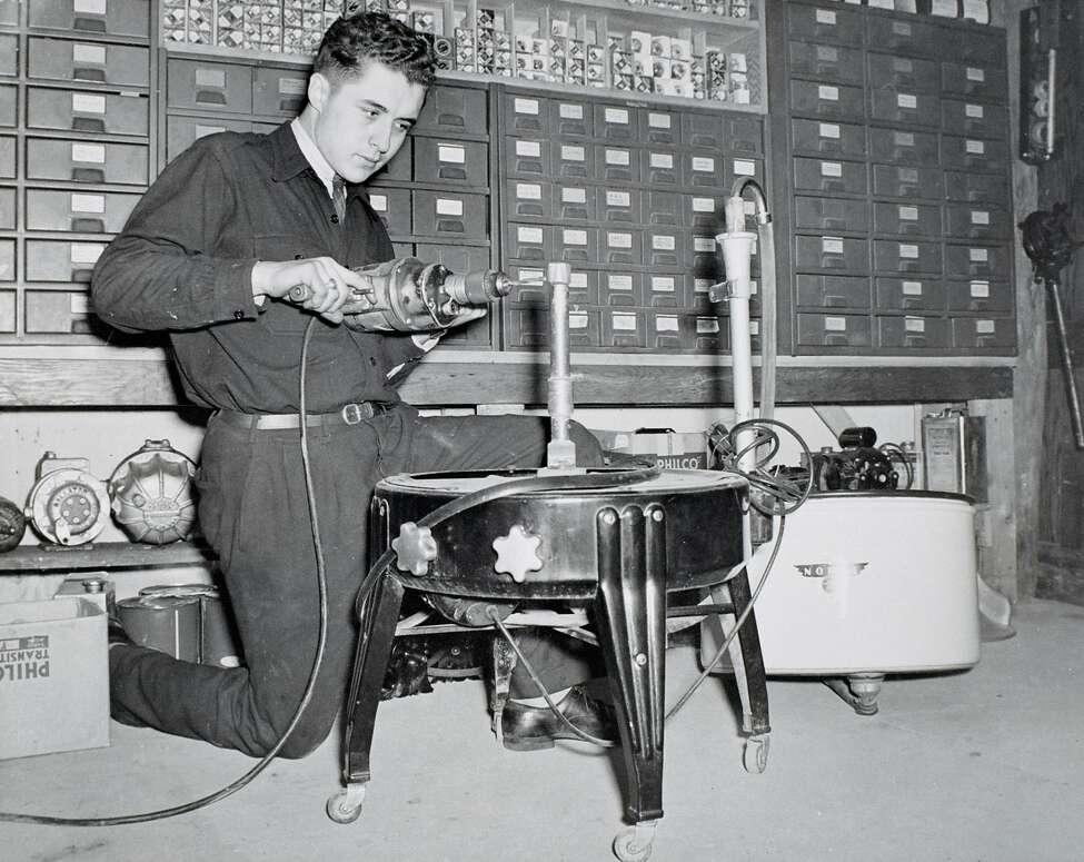 A young Earl B. Feiden assembles what appears to be a wringer washing machine. (Earl B. Feiden Appliances)