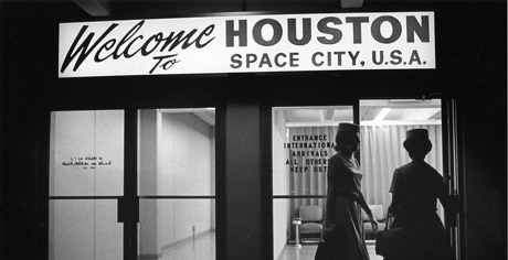 """Flight attendants enter the international arrivals area at Hobby Airport in December 1967. Arrivals are greeted with a """"Welcome to HOUSTON SPACE CITY, U.S.A."""" sign over the door."""