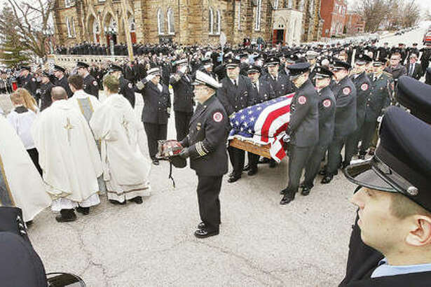 "The helmet of Godfrey Fire Capt. Jacob ""Jake"" Ringering is carried ahead of his flag draped casket as he is carried Tuesday from funeral services at St. Mary's Catholic Church and to a waiting Godfrey fire truck. Ringering was killed last week while fighting a house fire near Bethalto. Hundreds of firefighters and police officers from across the region turned out to honor Ringering in a large traditional firefighters funeral."