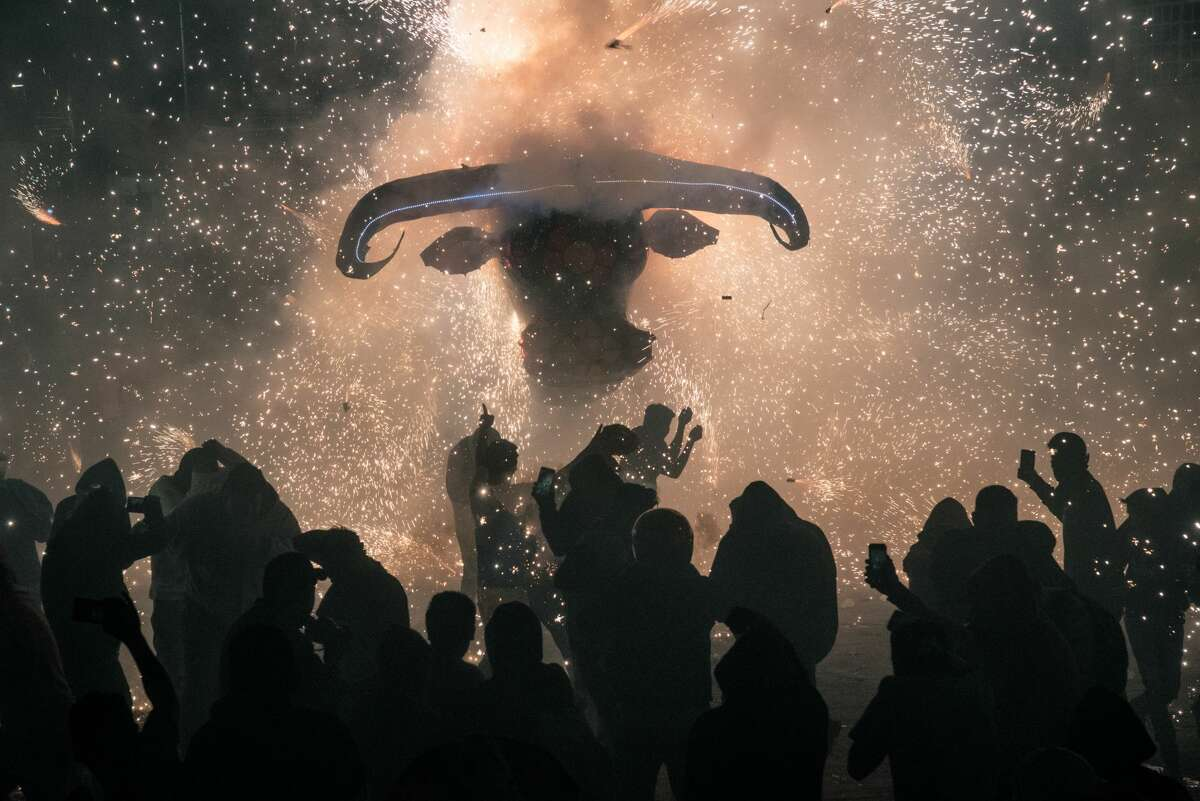 """Attendees use mobile devices to take photographs while sparks fly from a """"little bull"""" firework sculpture during the National Pyrotechnic Festival parade in Tultepec, Mexico state, Mexico, on Friday, March 8, 2019. Tultepec, a municipality of about 130,000 people, is famed for small workshops that produce many of the fireworks used on holidays throughout the region, according to the Associated Press. Photographer: Luis Antonio Rojas/Bloomberg"""