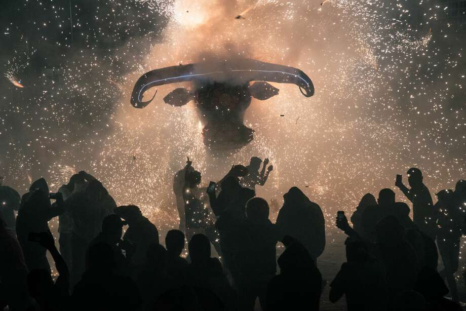 """Attendees use mobile devices to take photographs while sparks fly from a """"little bull"""" firework sculpture during the National Pyrotechnic Festival parade in Tultepec, Mexico state, Mexico, on Friday, March 8, 2019. Tultepec, a municipality of about 130,000 people, is famed for small workshops that produce many of the fireworks used on holidays throughout the region, according to the Associated Press. Photographer: Luis Antonio Rojas/Bloomberg Photo: Luis Antonio Rojas/Bloomberg"""