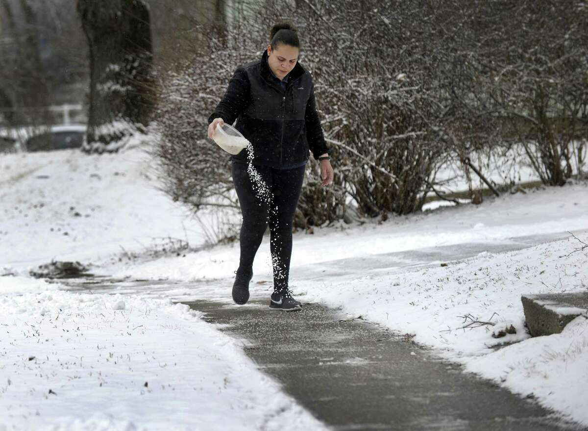After shoveling, Arleny Paulino of Danbury, sprinkles a salt mixture onto her walk and driveway to prevent them from freezing after an early morning snowfall Tuesday, January 30, 2018.